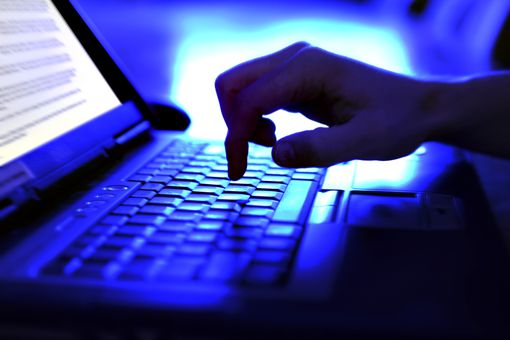 A close up of a laptop keyboard in a darkened room with one hand typing on it and a bright screen to the left hand side