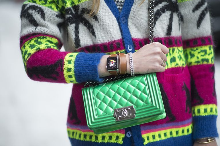 Woman with Apple Watch holding a green Chanel purse