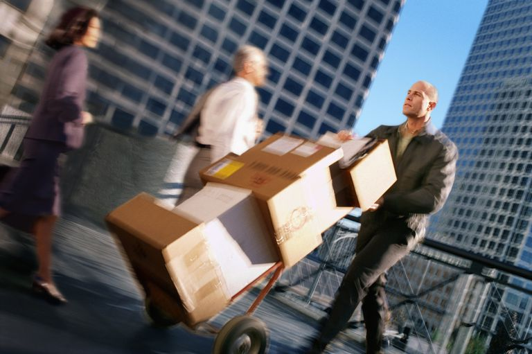 delivery man guiding a dolly stacked with boxes