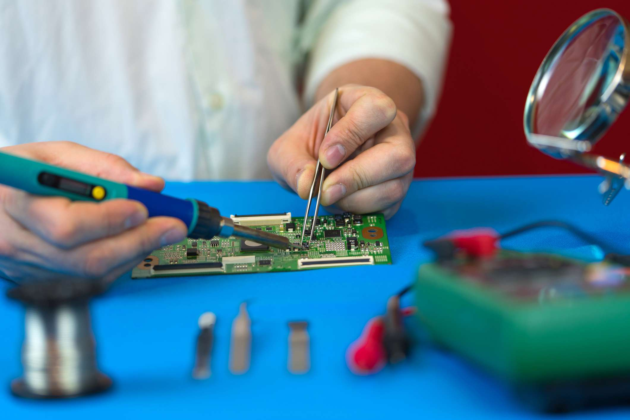 Close up of hands soldering on computer component