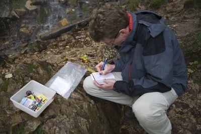 A man fills out a geocache logbook.