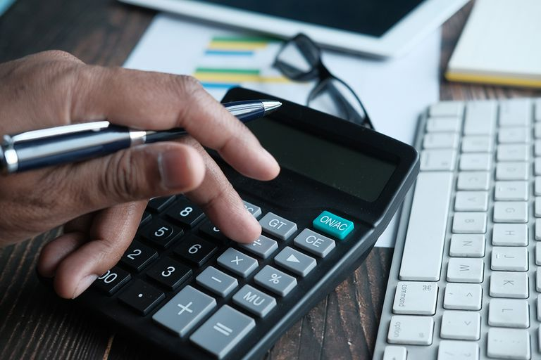 young accountant counting financial figures on office desk