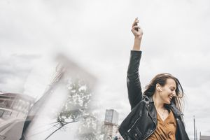 Woman listening to AirPods and holding her iPhone in the air.