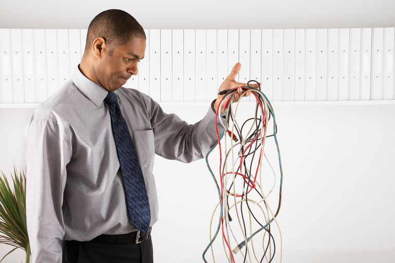 Businessman examining a tangle of electronic cords