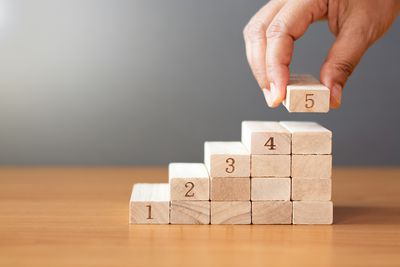 Hand putting a wooden block on top and arranging wooden blocks stacking on wooden table.