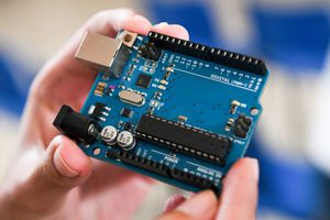 Close up of male hands holding an Arduino microcontroller board