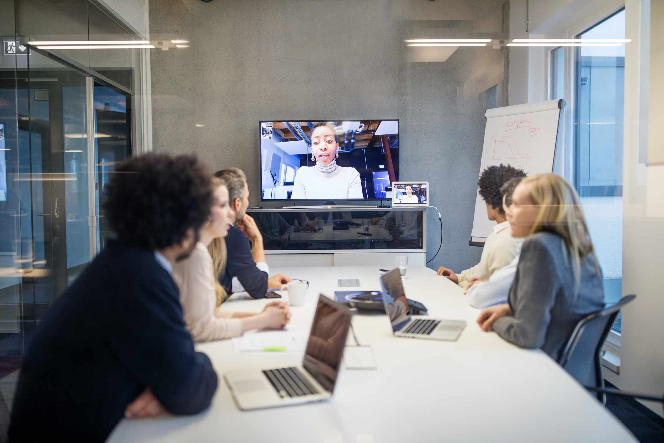 A conference room with a video conference call on the wall monitor