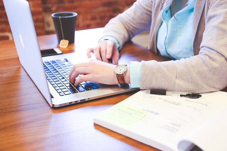 person typing on laptop keyboard next to a cup of hot tea
