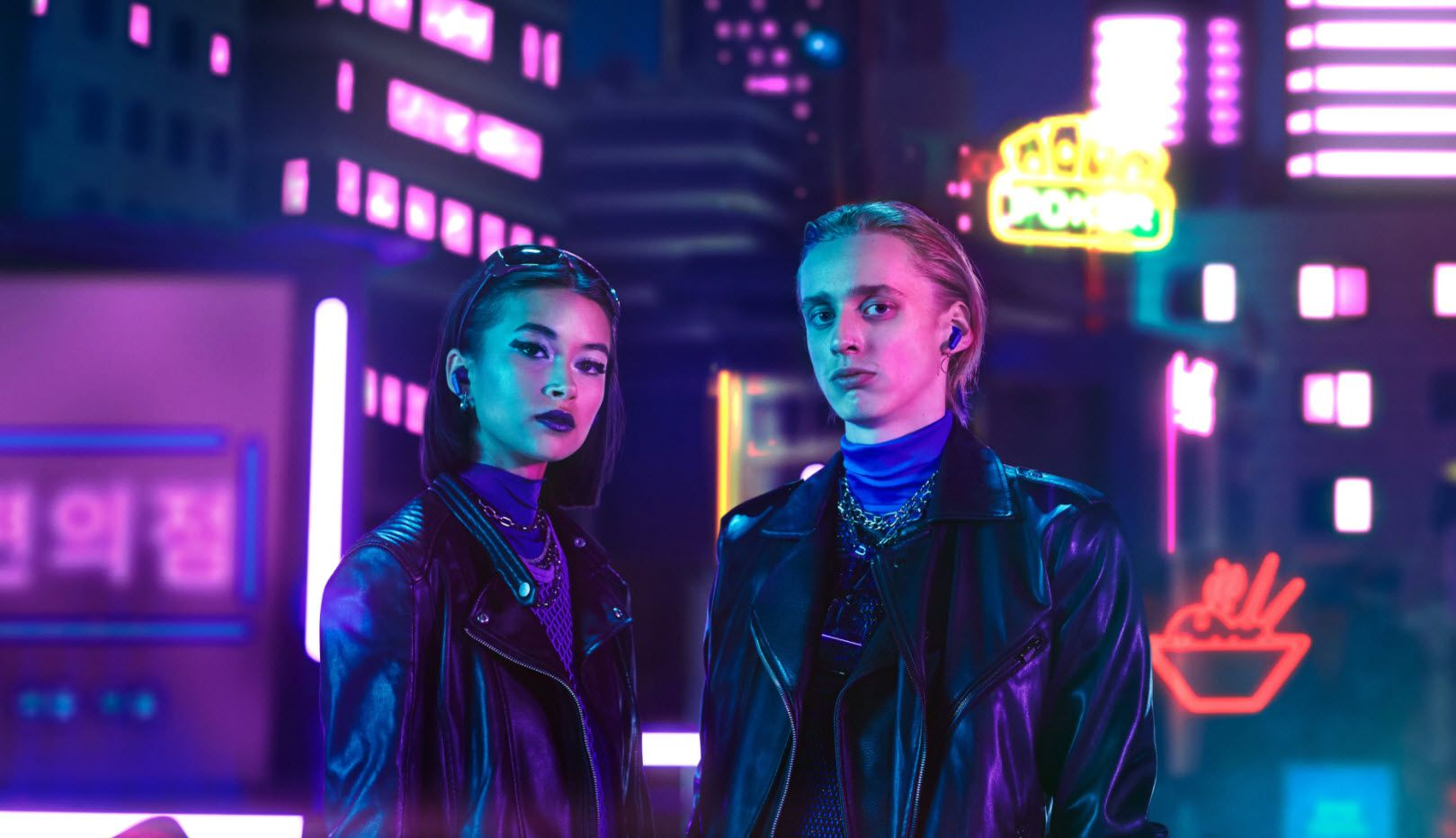 Models wearing the Urbanista Seoul earbuds on a dark city street light with black lighting.