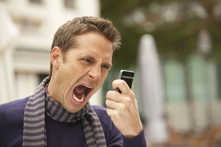 Angry man shouting at phone unwanted call