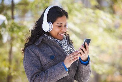 Young woman of South Asian ethnicity using cell phone and Bluetooth headphones holding phone