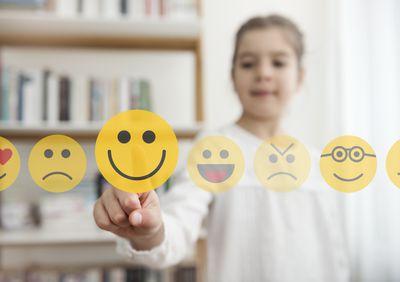 Child selecting smiling emoji.