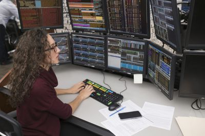 An IT support specialist types at a Bloomberg terminal with eight monitors.