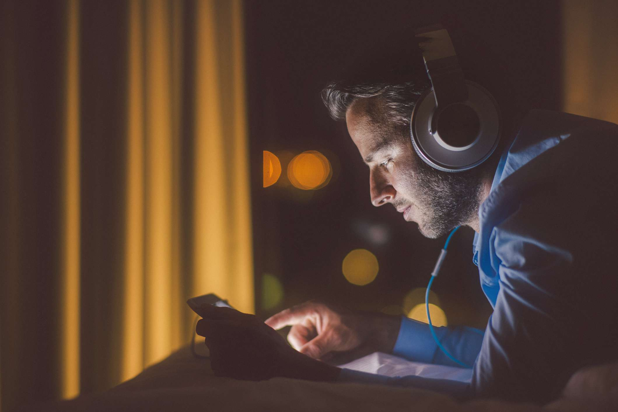 Someone using a tablet PC with headphones in a dark room.