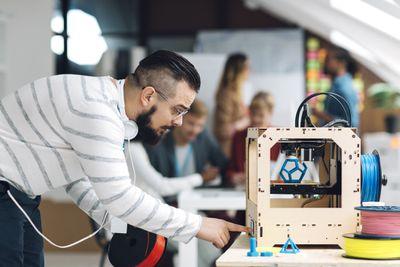 Man using 3D printer in office