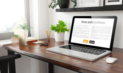 A laptop on a desktop displaying terms and conditions text