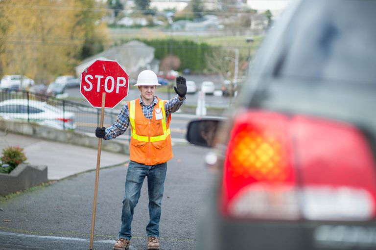 Adult male construction worker stopping traffic