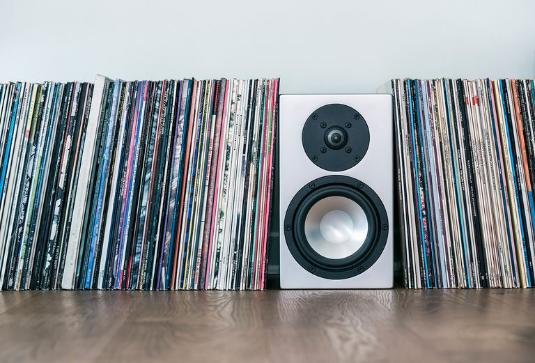 Vinyl records and loudspeaker box on hardwood floor