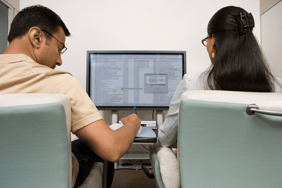 Two people looking at a spreadsheet