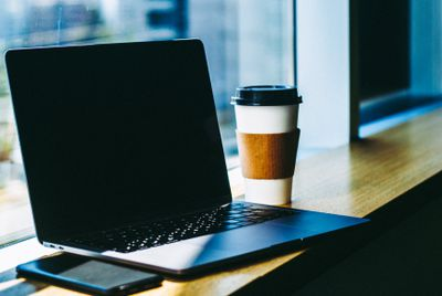 A laptop with a black screen sitting on a bar by a window with a to-go coffee cup and smartphone near it.