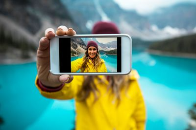 A young woman in a yellow jacket taking a cell phone selfie