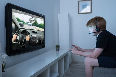 A child plays a racing game with an Xbox One headset not working.