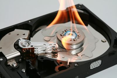 A burning disk drive that represents the destruction of the data stored on that disk.