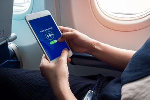 A person enabling Airplan Mode on their smartphone on a plane.