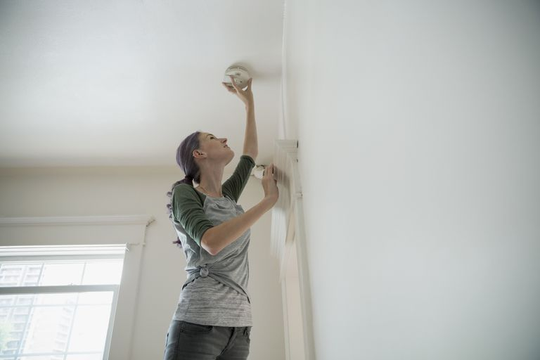 A woman fixes her beeping smoke detector.