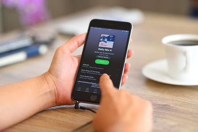 Woman using Spotify on iPhone 6.