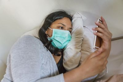 Someone laying in bed with a mask on, scrolling on their phone.