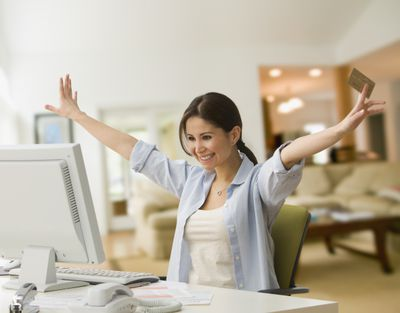 Woman holding credit card smiles sitting behind computer.