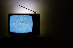 An old analog television set in a dimly lit room with static on the screen of the tv.