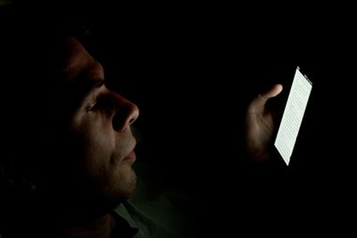A person looking at a smartphone in a dark room