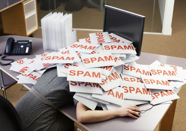 Young businesswoman at office desk with pile of spam envelopes
