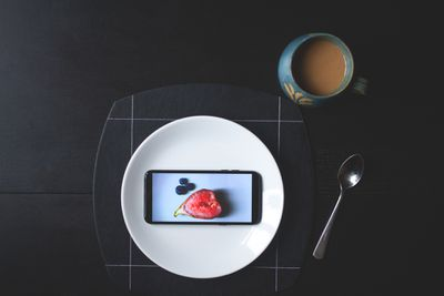A plate setting with a phone laying on top of it displaying food.