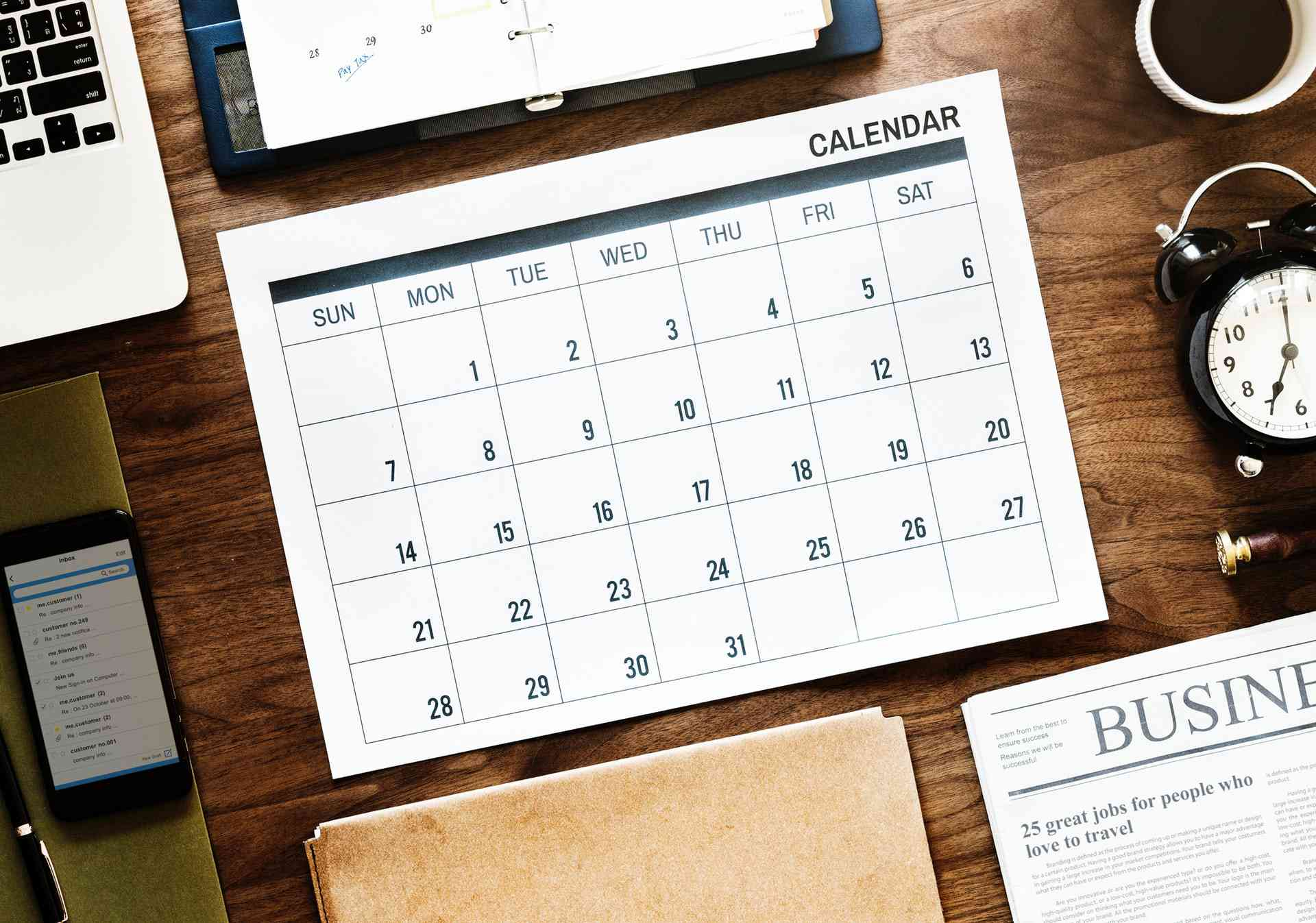 A calendar sitting on a desk with other office tools.