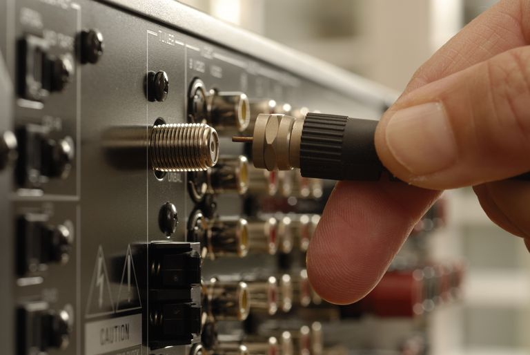 A cable being plugged into the back of a receiver/amplifier