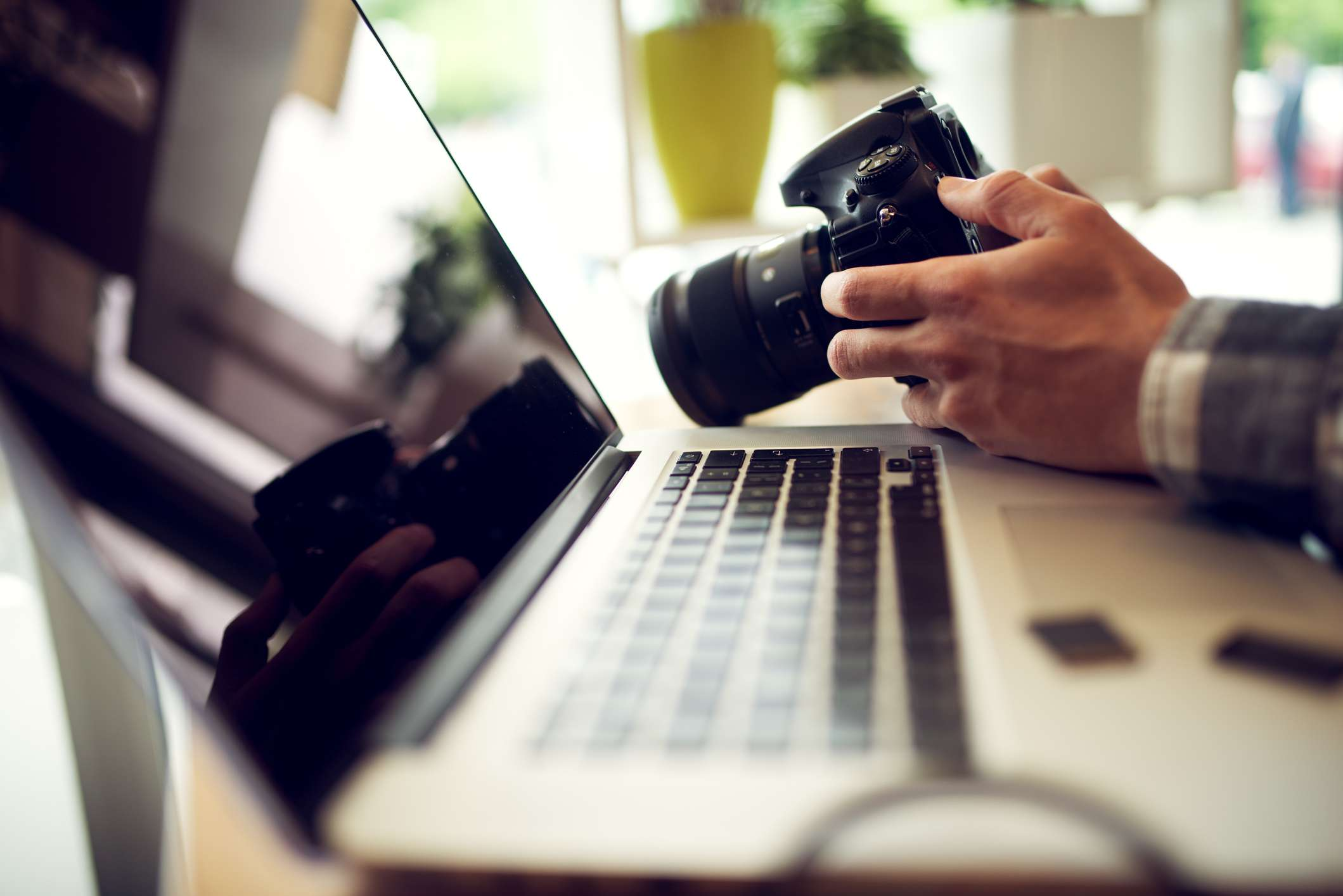 Close up photographer hands adjusting settings on his camera in office.