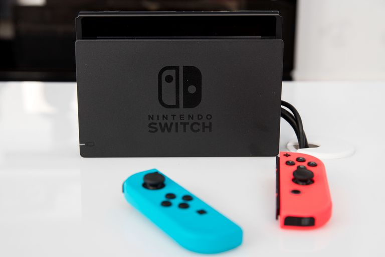 A Nintendo Switch console sits on a white surface.
