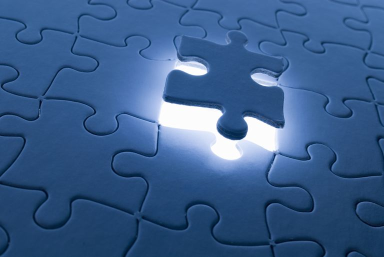 Puzzle piece floating above a puzzle
