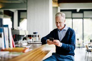 Man looking at his iPhone while sitting at a bar