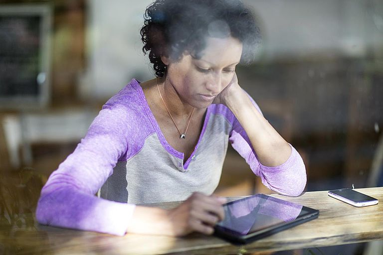 Woman looking at a tablet computer shot through the window of a cafe