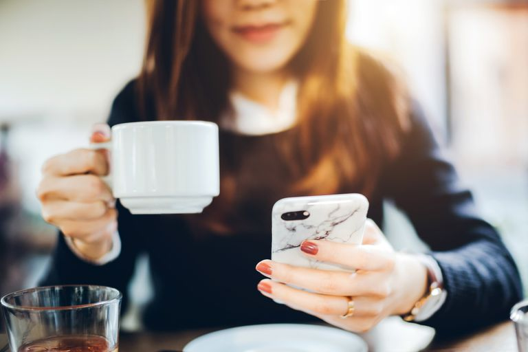 Woman drinking coffee and checking email on phone.