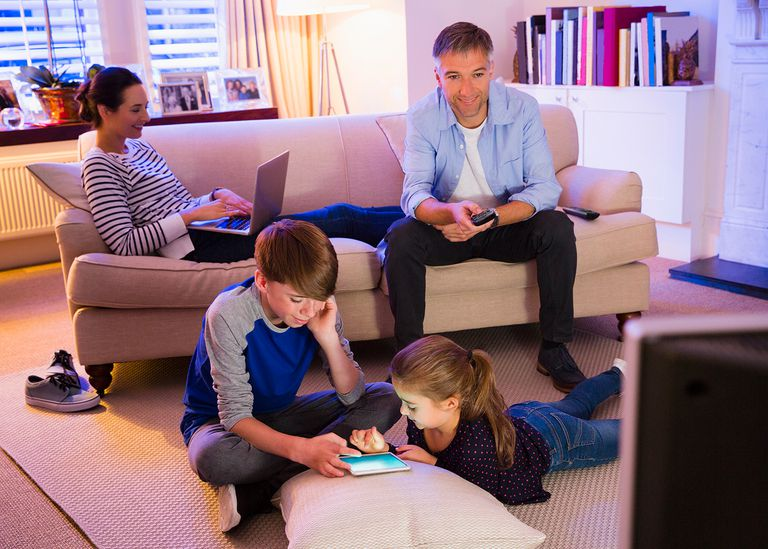 Family relaxing with technology in living room