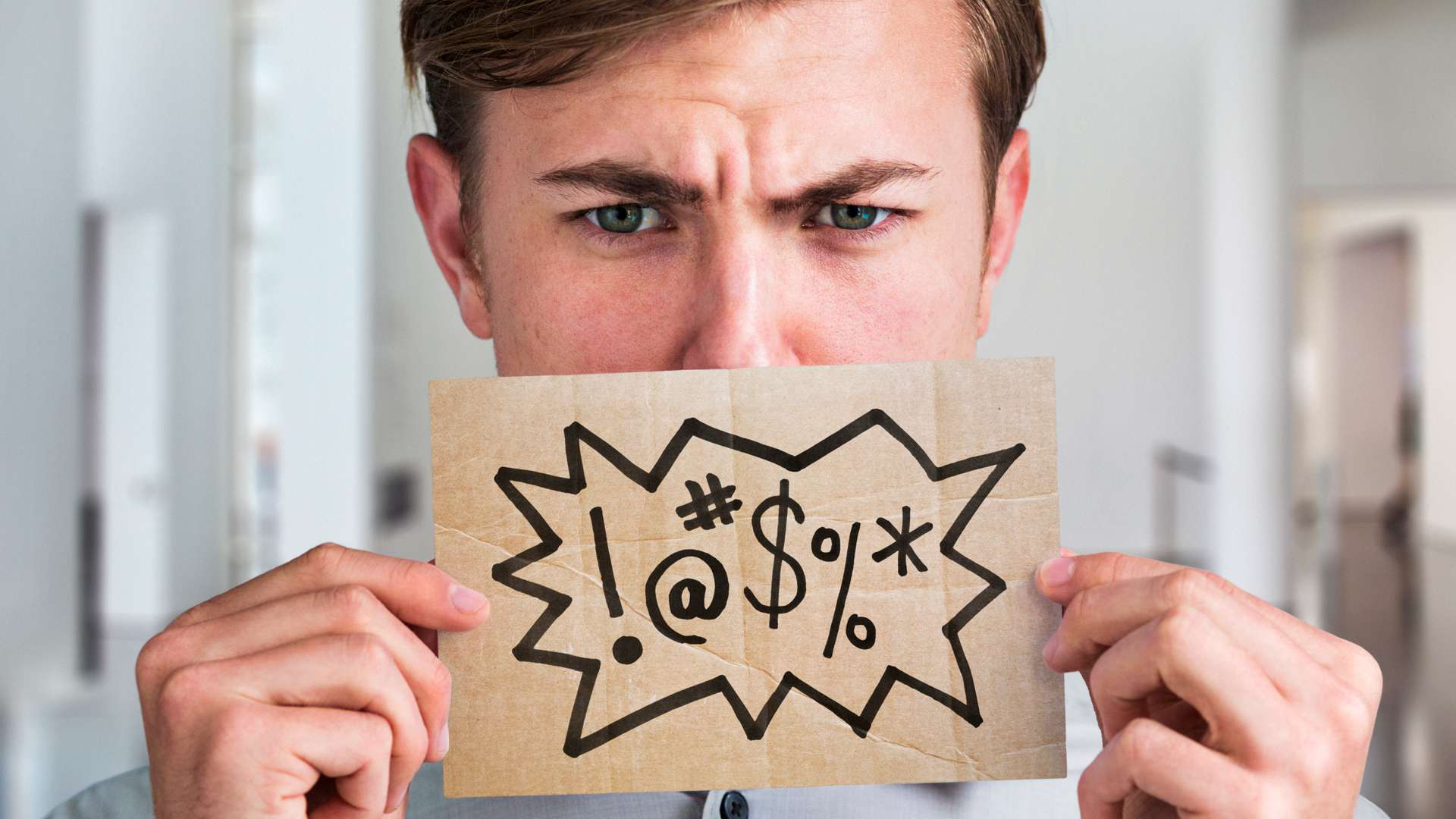 Man holding up a piece of cardboard with curse symbols on it.