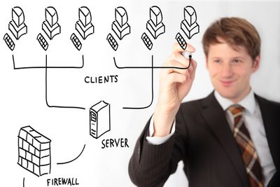Network analyst drawing a client server diagram on clear board