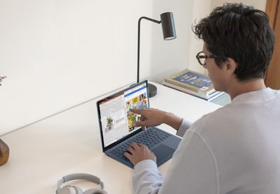 A man sitting at a desk touching the screen of his Microsoft Surface Laptop running Windows 11.