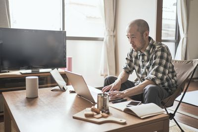 A man sitting at a coffee table looking at his laptop resting on the table