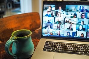 A large Zoom meeting displayed on a laptop in someone's living room with a cup of coffee nearby.
